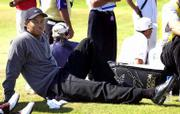 Tiger Woods relaxes while waiting to tee off on the fifth hole Friday in the British Open. Woods takes a three-shot lead into the third round.