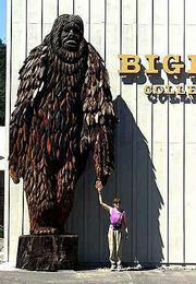 A tourist poses with a two-story high statue of Bigfoot outside the Bigfoot Wing of the Willow Creek-China Flat Museum in Willow Creek, Calif. The struggling ex-lumber town expanded its existing museum to include the new Bigfoot Wing with the hopes of attracting more tourists to the area.