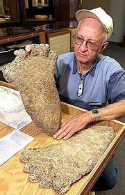 Al Hodgson, a volunteer guide at the Willow Creek-China Flat Museum, holds up a plaster cast of a Bigfoot imprint.