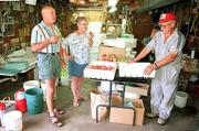 Tib and Pat Price, left and center, of DeSoto sample some of the fresh peaches sold by Floyd Ott, right. Ott sells the fruit at his home, at the Lawrence Farmers Market and at the Community Mercantile Co-op.