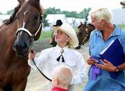Katie Sloan, 10, Lawrence, a member of the Lone Star 4-H Club is congratulated by her mother, Polly Sloan, right, after Katie and her horse, Susanna, won grand champion in the halter class at Saturdays 4-H horse show at the Douglas County Free Fair. The fair continues through Saturday. The open horse show is at 2 p.m. today.