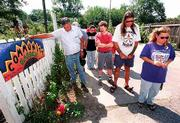 About a dozen Lawrence residents concerned with the progress of the John Lowe hit-and-run murder case gathered Wednesday afternoon to walk the alley where he was dragged to his death. Bowing their heads in a prayer led by Dempsey Micco, left, are, from left, Mariana Hinojosa, City Commissioner Mike Rundle, Terrance Savage and Annette Thille White.