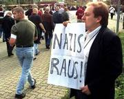 A demonstrator holds a sign reading Nazis Out in response to a protest Saturday by the National Democratic Party, a neo-Nazi group, in Tostedt, Germany.