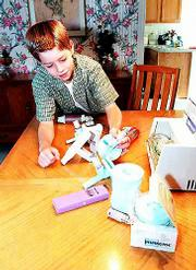 Anthony Frei, 11, looks over the different types of inhalers that members of his family use.