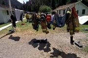 Firefighter Mike Duke waits for his firefighting gear to dry as it hangs on a line Saturday, near Cobalt, Idaho. More than 62,000 wildfires have charred 3.8 million acres so far this year in what officials are calling the worst Western fire season in 50 years.