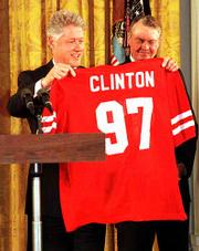 President Clinton, left, and former Nebraska football coach Tom Osborne show off Cornhuskers football jersey during a ceremony honoring NU as the NCAA college football co-champions in 1997.