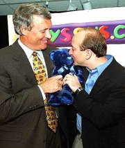 John Eyler, left, chief executive officer of Toys R Us Inc., holds a stuffed bear as Jeff Bezos, founder of Amazon.com, kisses it during a news conference Thursday in New York. Amazon.com and Toys R Us are collaborating to set up online stores selling toys, video games and baby products.