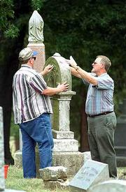 "Darrell Giles, Lawrence, left, and Alan Russ, Auburn, clean up the grave marker of the Palmer family in Oak Hill Cemetery, where Daniel Palmer and his son Charles are buried, both victims of Quantrill&squot;s Raid on Lawrence in 1863. The ""Sons of Union Veterans"" cleaned markers Saturday."