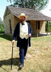 Edward Hoover, Lecompton, walking in front of a historic stone cabin in Lecompton, often participates in re-enactments that involve portrayals from the Kansas Territorial period.