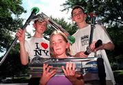The six-pound scooters can be collapsed and easily stuffed in a backpack. Displaying their Razor brand scooters are, from left, Patrick Roberts, 15, Rose Naughtin, 9, with scooter collapsed, and her brother Hugh, 15.