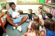 KU defensive back Carl Nesmith reads Dr. Seuss's Green Eggs and Ham to first graders Wednesday at Centennial School.