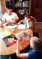 "Jim Joyce, left, assists his son, Alek, 8, top right, a third-grader at Pinckney School, complete a 20-word spelling assignment in the Joyce home recently. First-grader Kale Joyce, 6, sits at the table to read part of ""A Bug, A Bear and A Boy Go to School."" According to the U.S. Department of Education, one of the most important considerations in doing homework is the setting of a regular time."