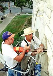 Gustavo O'Riley, left, and Keith Middlemas drill holes into an archway on the Douglas County Courthouse. Middlemas, an area stonemason, plans to finish the restoration of the courthouse's limestone next week.