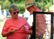 Eugenia and Bill Bryan, Lawrence, look at a necklace at the arts and crafts festival in Lawrence. The two were looking at items Sunday at Lawrence resident Tom Wells' crafts booth.