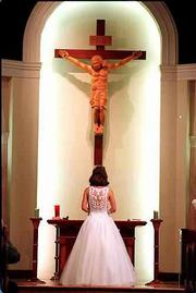 Katie Self of Lawrence stands before the Altar of St. John the Evangelist Catholic Church during the Mass for her quincea. The ceremony for 15-year-olds, which has its roots in Mexico, marks a girl's transition to adulthood.