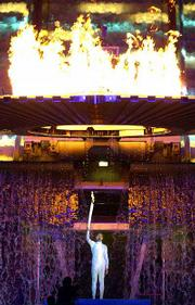Australian runner Cathy Freeman holds the Olympic torch aloft as the flame rises to light the cauldron during the opening ceremony for the Summer Olympics Friday, Sept. 15, 2000, at Olympic Stadium in Sydney, Australia.