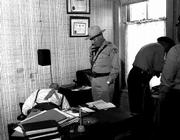 A sheriff's deputy uses Leroy Harris' office telephone as two Lawrence Police officers collect evidence for his murder investigation. The crime scene photos were taken by Rich Clarkson, now a nationally known photographer, who was a Kansas University student working part-time for the Journal-World in 1954.