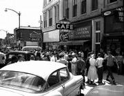 In the aftermath of the 1954 murder of attorney Leroy Harris, a crowd gathers in the 700 block of Massachusetts. The door to the right of the Green Lantern Cafe led to the stairs to Harris' office above 743 Mass., which has remained sealed since shortly after the crime.