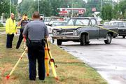 Lawrence Police officers, from left, Brian Kelly and Richard Nichols, along with Randy Glidewell, take measurements in the 1000 block of North Third Street. The officers were investigating a Friday accident that resulted in the death of pedestrian Roger Borland, 53. Borland was struck by the pictured pickup truck while he was crossing the street.