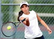 LAWRENCE HIGH'S MARIA SALCEDO smashes a forehand during her No. 1 singles match against Shawnee Mission West on Wednesday at Lawrence Tennis Center. Salcedo won, 8-3.
