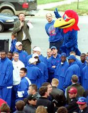Friday's Big Blue Rally drew Jayhawk fans downtown to listen to Kansas University football coach Terry Allen, rear left, and announcer David Lawrence, rear center, about today's game against Kansas State University. Team members and supporters crowded the intersection of Eighth and New Hampshire streets for the pep rally. Today's game begins at 1 p.m.