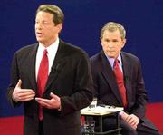 Democratic presidential candidate Vice President Al Gore, left, makes a point under the watchful eye of Republican presidential candidate Texas Gov. George W. Bush. The two on Tuesday were participating in their third and final debate at Washington University in St. Louis.