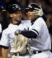 The Yankees' David Justice, right, celebrates his three-run home run with teammate Derek Jeter. Justice's homer in the seventh inning put New York ahead to stay in its pennant-clinching 9-7 victory over Seattle on Tuesday night at Yankee Stadium.
