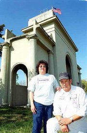 Mary Jackson and her husband, Eli, both with the facilities department at Haskell Indian Nations University, want to restore the Haskell Stadium Arch, shown in the background. The Jacksons initiated the Arch and Stadium Committee that is raising money for the restoration.