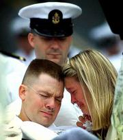 A wounded sailor from the USS Cole grieves with his wife during a memorial at Norfolk Naval Station in Norfolk, Va., for victims of the bombing aboard the USS Cole. Seventeen sailors were killed in what U.S. officials believe was a terrorist suicide attack in Yemen. The sailor viewed the memorial Wednesday from his hospital bed that was rolled to the event.