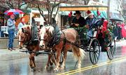 Lawrence businesspeople are pulling together in support of the annual Old Fashioned Christmas Parade, which was in danger of not taking place this year because of money problems. This photo shows a horse-drawn carriage from the 1999 parade.