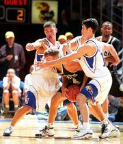The Jayhawks' Jeff Boschee, left, and Kirk Hinrich apply pressure against Emporia State's Ryan Adkison. Kansas rolled to a 120-51 exhibition victory over Emporia State on Saturday night at Allen Fieldhouse.