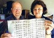 "Frank Kaubin&squot;s ""Victory Song"" moved from his head onto musical script thanks to the efforts of Tom Stidham, who leads bands at Kansas University. Stidham, left, and Kaubin&squot;s daughter, Franda Flyingman, Lawrence, right, hold the finished score. Stidham, an associate professor of music, took the tune rattling around Kaubin&squot;s head and helped him bring it to life for band musicians."