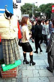 Resplendent in her 8-inch heels and leather skirt, a young shopper pauses to chat on a Tokyo street corner.