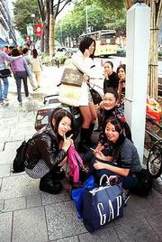A group of young women take time out from their shopping in Tokyo's Shibuya to rest and, in some cases, smoke a cigarette. Smoking is still very popular in Japan.