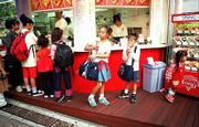 PRE-teen youngsters stop to buy ice cream at a stand in Tokyo on their way home from school.