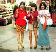 Three young shoppers pause to flash the victory sign while making their rounds in a mall in Kyoto. In spite of Japan's economy facing a downward trend, it doesn't seem to hamper young shoppers who fill trendy shops that sell boots, stockings and new and used clothing.
