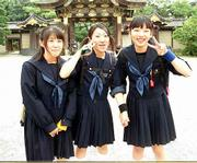 Two young women in school uniforms, a long-time Japanese tradition, tour a temple with class members in Kyoto. For some, streetwear is after-school fashion.