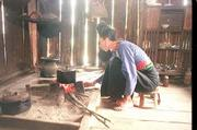A few bricks prop a blackened pot above a fire in the kitchen as a member of the On family tends to her cooking in a Black Tai village. The openings between the wallboards serve as ventilation.