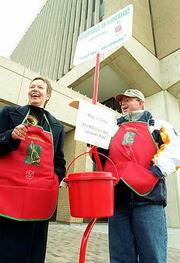 Ringing bells at the kick-off of the Salvation Army's annual kettle drive are advisory board members Judy Bauer, left, and Glynn Sheridan. Friday's kickoff in front of Firstar Bank at Ninth and Massachusetts streets included live music. The Salvation Army has set a goal of $145,000 for its holiday fund drive.
