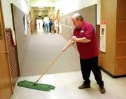 Jim Thomas, head custodian at East Heights Elementary School, sweeps a hall recently. He has been a district employee for five years and a custodian for 15 years.The Lawrence school district has a shortage of custodial and food service workers and is having a hard time filling the positions.