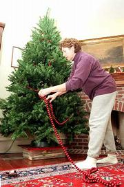 Candy Davis starts with the tree as she decorates her home at 947 La. for the Holiday Home Tour that begins next weekend. The tour will feature six homes and Plymouth Congregation Church, 925 Vt.