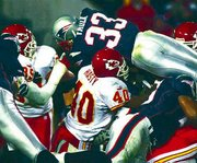 New England running back Kevin Faulk (33) goes over the top of the Chiefs defense to score a first-quarter touchdown. Faulk's TD came in the Patriots' 30-24 victory on Monday in Foxboro, Mass.