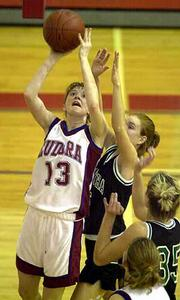 Eudora High senior Jessica Bryant (13) slides past KC Maranatha defenders to launch a short jump shot. Bryant scored 16 points in the Cardinals' 51-33 victory Monday in Eudora.