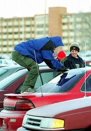 Trevor Johnson, a KU Freshman from Oconomowoc, Wis., left, puts his entire body into his work as he chips at the ice on his car's back window. Johnson and his friend Brent Stevens, a Wichita sophomore, right, were clearing the windows Monday after classes.