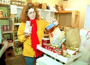 "Judy Leuer, a volunteer at Pelathe Community Resource Center, 1423 Haskell Ave., looks over stacks of food on Friday that were brought to the center. Lawrence residents responded generously after the center&squot;s food shortage was publicized. ""Our pantry has really needed some help,"" Leuer said. ""It&squot;s been a great blessing, all the people coming in."""