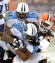 Cleveland's Marquis Smith grabs the facemask of Tennessee running back Eddie George (27) in the second quarter. George ran for 176 yards and three touchdowns in the Titans' 24-0 victory Sunday in Cleveland. Smith was called for a five-yard facemask penalty.