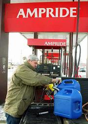 Frank Salb, fills his gasoline cans at the Ampride station, 1000 E. 23rd St. in Lawrence. Money from Monday's purchase went to the Farmers Cooperative Assn., which wants to sell its store to cut the co-op's debt.