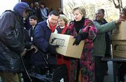 Senator-elect Hillary Rodham Clinton, D-N.Y., right, helps Larry Jones, center, president of Feed The Children, put a box with food into a mans cart Thursday, Dec. 21, 2000, in New York's Harlem neighborhood. Clinton was on hand to help Feed the Children hand out food to residents for the holidays.