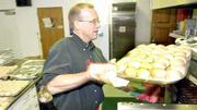 Jeff Potteiger, Lawrence, has his hands full as he removes a tray of piping hot rolls from the oven at First United Methodist Church. Potteiger teamed with his wife, Ellen Adams, to run the kitchen Monday for the annual dinner.