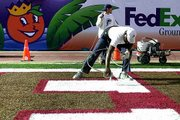 Ground crew workers Nate Jackson, front, and Rob Enterline paint the end zone at Pro Player Stadium on Tuesday. Oklahoma will face Florida State for the national championship tonight in the Orange Bowl in Miami.